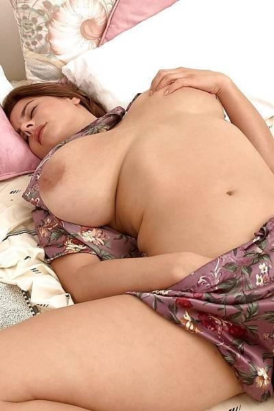 Грудастая девушка нежится и ласкает себя в постели