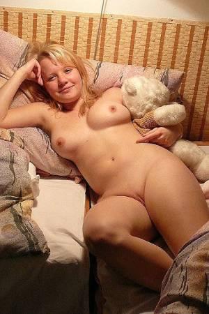 Молодая блондинка с побритой писькой позирует голая в спальне