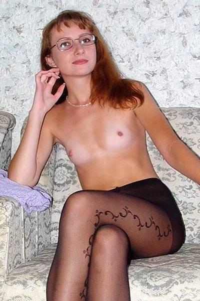 Худенькая рыжая девка с плоскими титьками позирует в колготках на голую попу