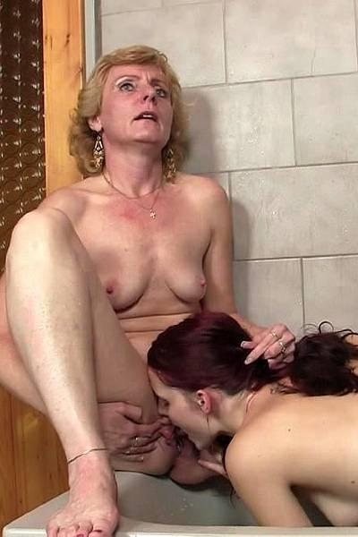 В ванной зрелая женщина трахает девушку самотыком, а та лижет ей пизду